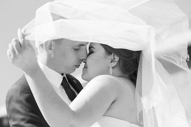 Černobílé foto-líbající se pár-ženich s nevěstou ukrytí pod závojem.jpg
