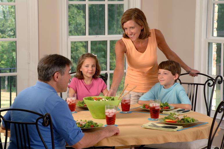 rodina u stolu, rodiče a dvě děti v kuchyni sedí a chystají se jíst, žena donesla salát