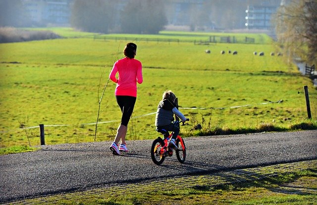 žena běží a dítě jede na kole
